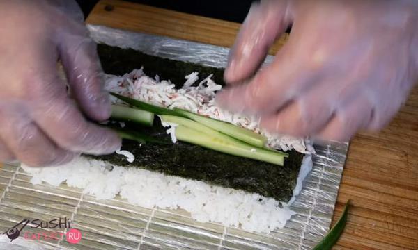 Укладываются крабовые палочки и авокадо